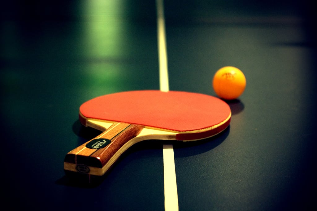 A ping pong ball and paddle on a table