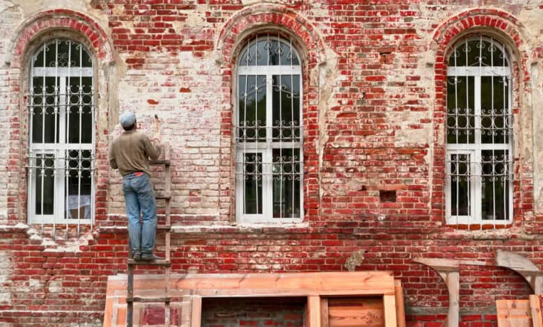 worker working on a red brick fassade