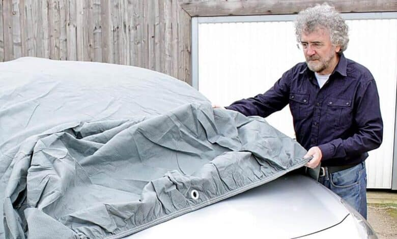 man covering car with gray cover