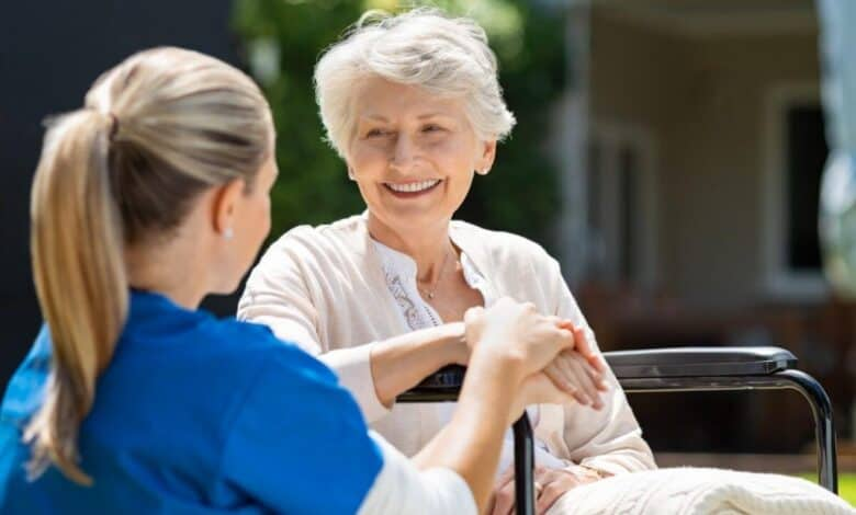 elderly woman smiling to a nurse